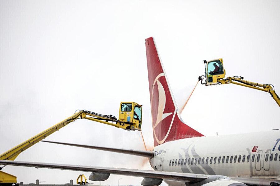 Uçakların kuyruk ve kanatları buzlanmaya karşı özel bir sıvıyla yıkanıyor