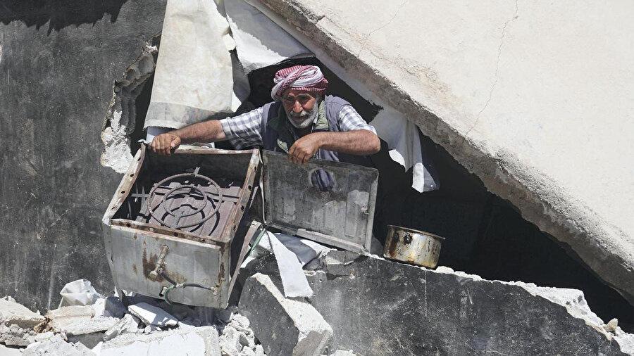 Yıkıntıların arasından eşyalarını kurtarmaya çalışan Suriyeliler.