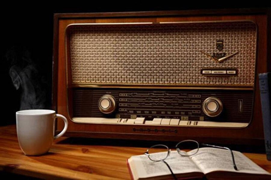 Uzun süren bir sessizlikten sonra, çayları doldururken, radyonun düğmesine dokundu.