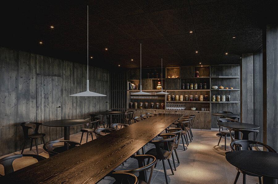 Restoranda koyu renk paletiyle loş ve samimi bir atmosfer oluşturuluyor.