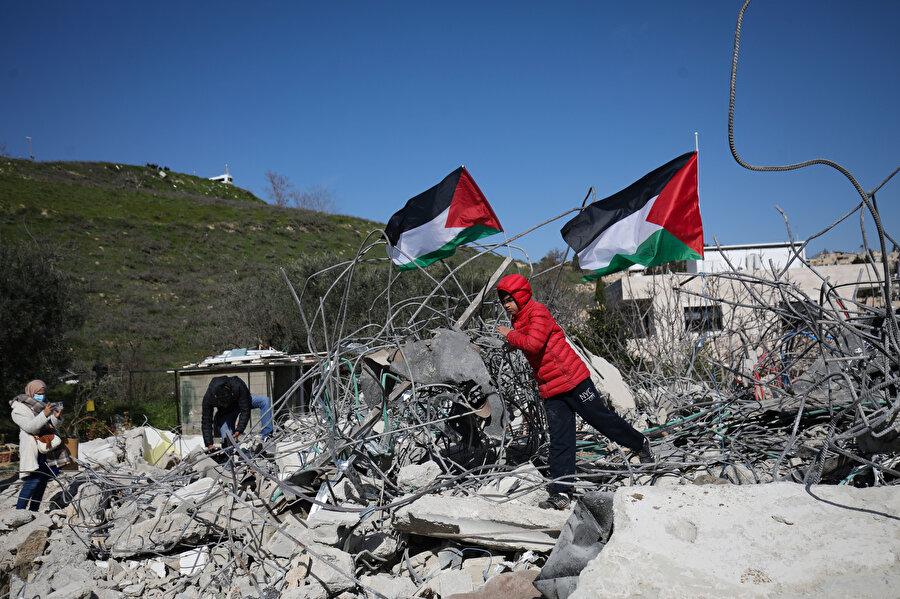 Yıkılan binaların üzerinde dalgalanan Filistin bayrakları.