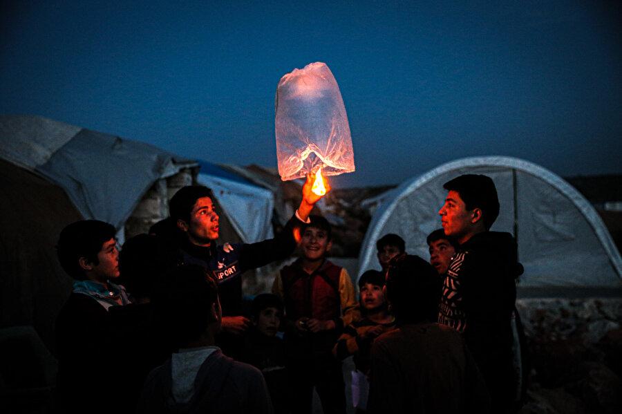 Suriyeli çocuklar iç savaşın yıl dönümü nedeniyle gökyüzüne dilek balonu uçurdu.
