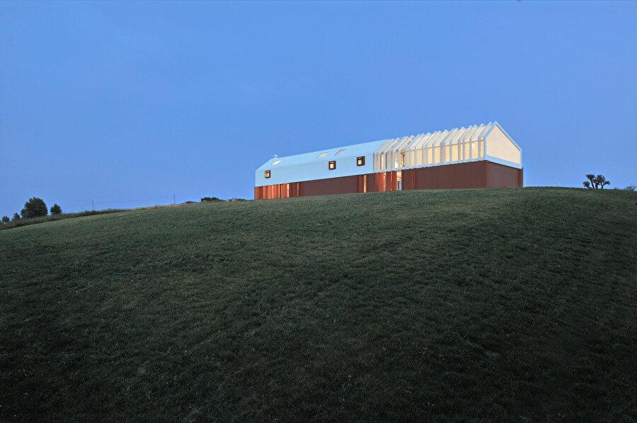 Çatıda kullanılan yarı saydam malzeme ile evin üst kısmı içeriden parlıyor gibi görünüyor.