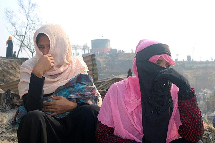 Küle dönen barınakların kenarında göz yaşlarına hakim olamayan mülteci kadınlar.