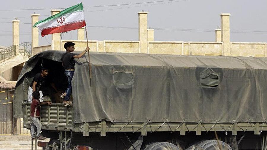 Deyrizor ilinde İran'dan gelen yardımların taşındığı kamyonun arkasında İran bayrağı taşıyan Suriyeli bir çocuk.