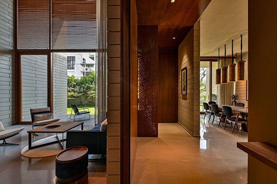 Brüt beton ev, iç dekorasyonda tercih edilen doğal kumtaşı ve yumuşak ahşap paletler ile ön plana çıkıyor.