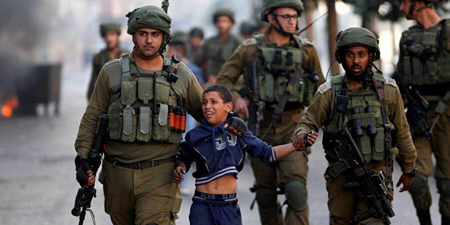 İsrail askerlerince gözaltına alınan Filistinli bir çocuk.
