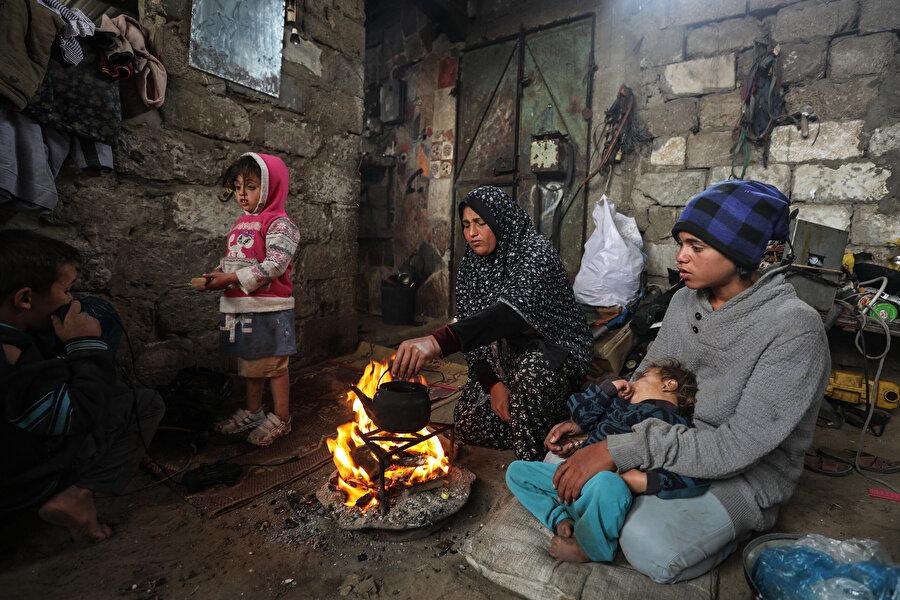 Filistinli anne evin ortasında yaktığı ateşle çocuklarına yemek yapmaya çalışırken.