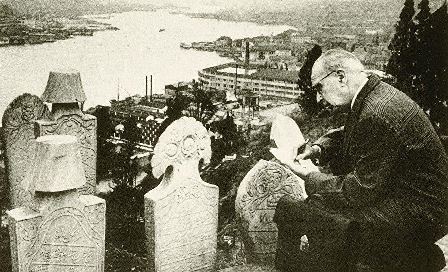 Süheyl Ünver, bir Eyüp Sultan ziyaretinde mezar taşının başında defterine not alırken.