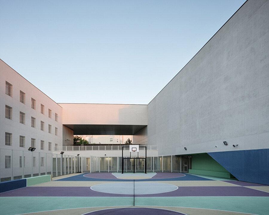 Hapishane, pastel renklerle boyanmış bir spor sahasını çevreleyen iki blok halinde tasarlıyor.