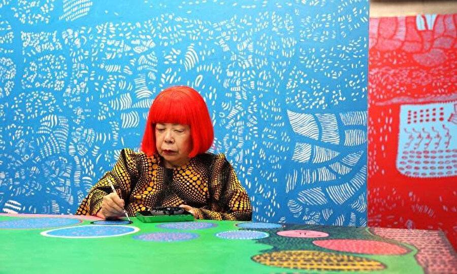 """Yayoi Kusama, """"Evrene Gittiğimde Hareketli An"""" adlı tablosunun önünde çalışırken."""