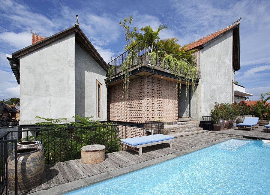 Girişe bakan duvarlardaki tuğla bloklar, yapıya doğal gün ışığı sağlayarak samimi bir atmosfer oluşturuyor.