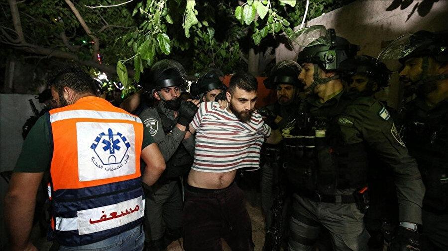 Çıkan kavga sonrasında İsrail polisi tarafından tutuklanan bir Filistinli genç.