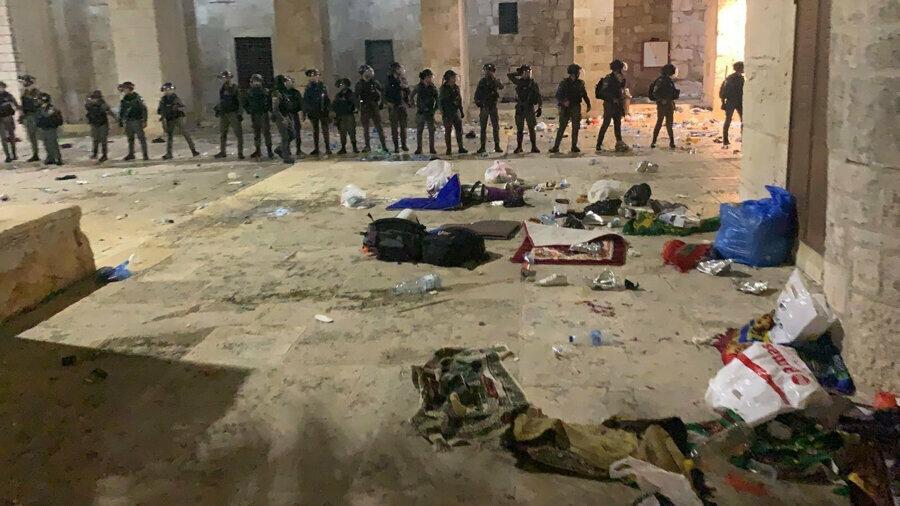 Namaz esnasında saldırıya uğrayan cemaatin dağılmış eşyaları ve baskını gerçekleştiren İsrail polisi.