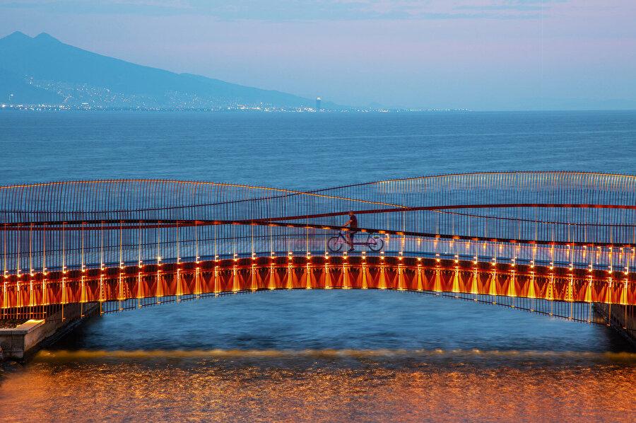 Aydınlatma sistemi, sudaki yansımanın da etkisiyle, köprünün hareketli formunu ön plana çıkarıyor.
