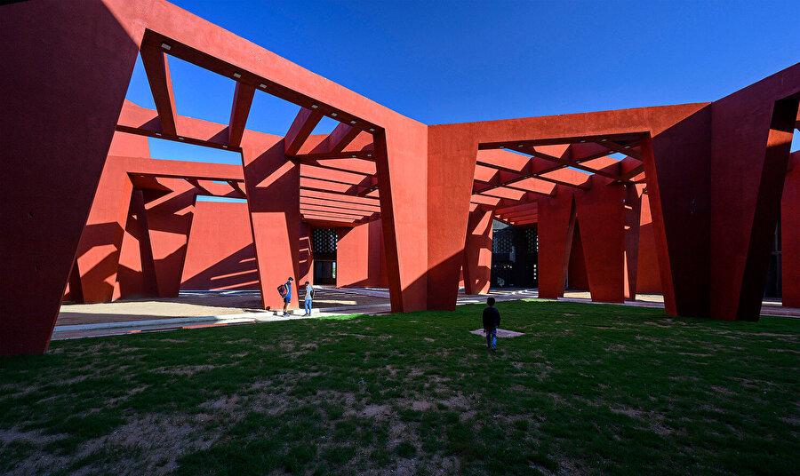Kırmızı birimlerden oluşan ağ, okul kampüsünde gölgeli yarı açık bir alan tanımlıyor.