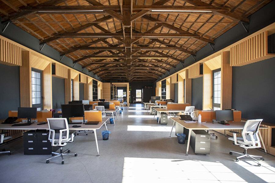 İki katlı yapının ahşap çatıyla kaplı üst katında, açık bir çalışma alanı bulunuyor.