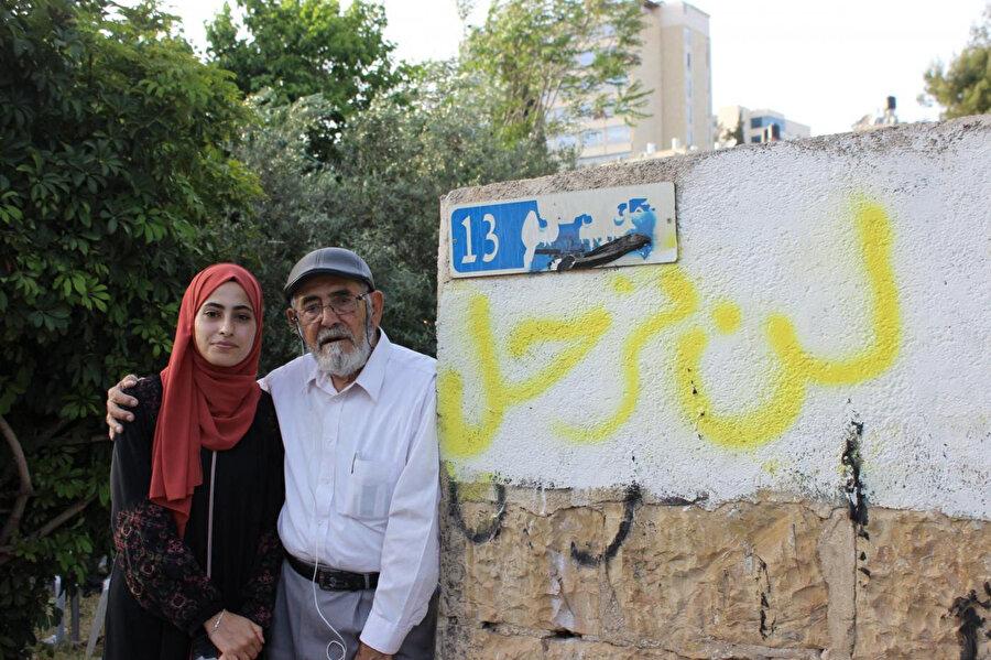 """Muna el-Kurd ve babası. Evlerinin duvarında yazan yazı: """"Terk etmiyoruz""""."""