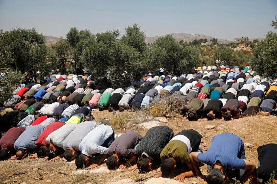 2 gün önce, Batı Şeria'nın Beyta kasabasında İsrail askerlerinin ve Yahudi yerleşimcilerin zeytin ağaçlarına gerçekleştirdiği saldırılara direnen Filistinliler, cuma namazını kılıyor.