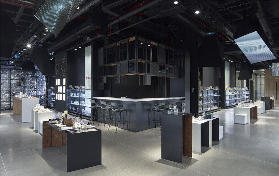 Showroom'un merkezinde ziyaretçilerin dinlenebileceği oturma birimleri ve bir bar alanı bulunuyor.