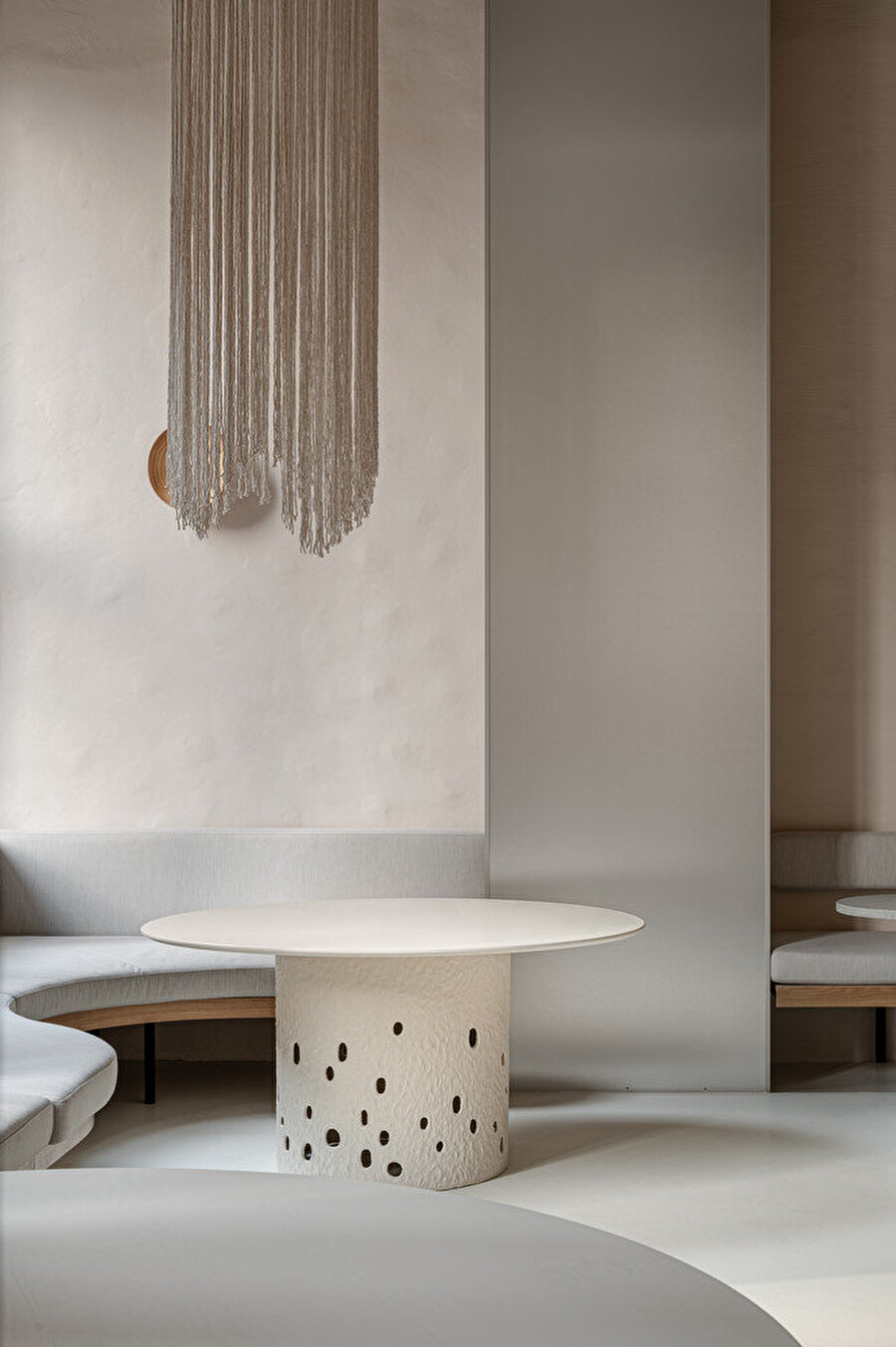 Koltukların basit ve geometrik şekilleri masa ve aksesuarların yuvarlak hatlarıyla yumuşatılıyor.