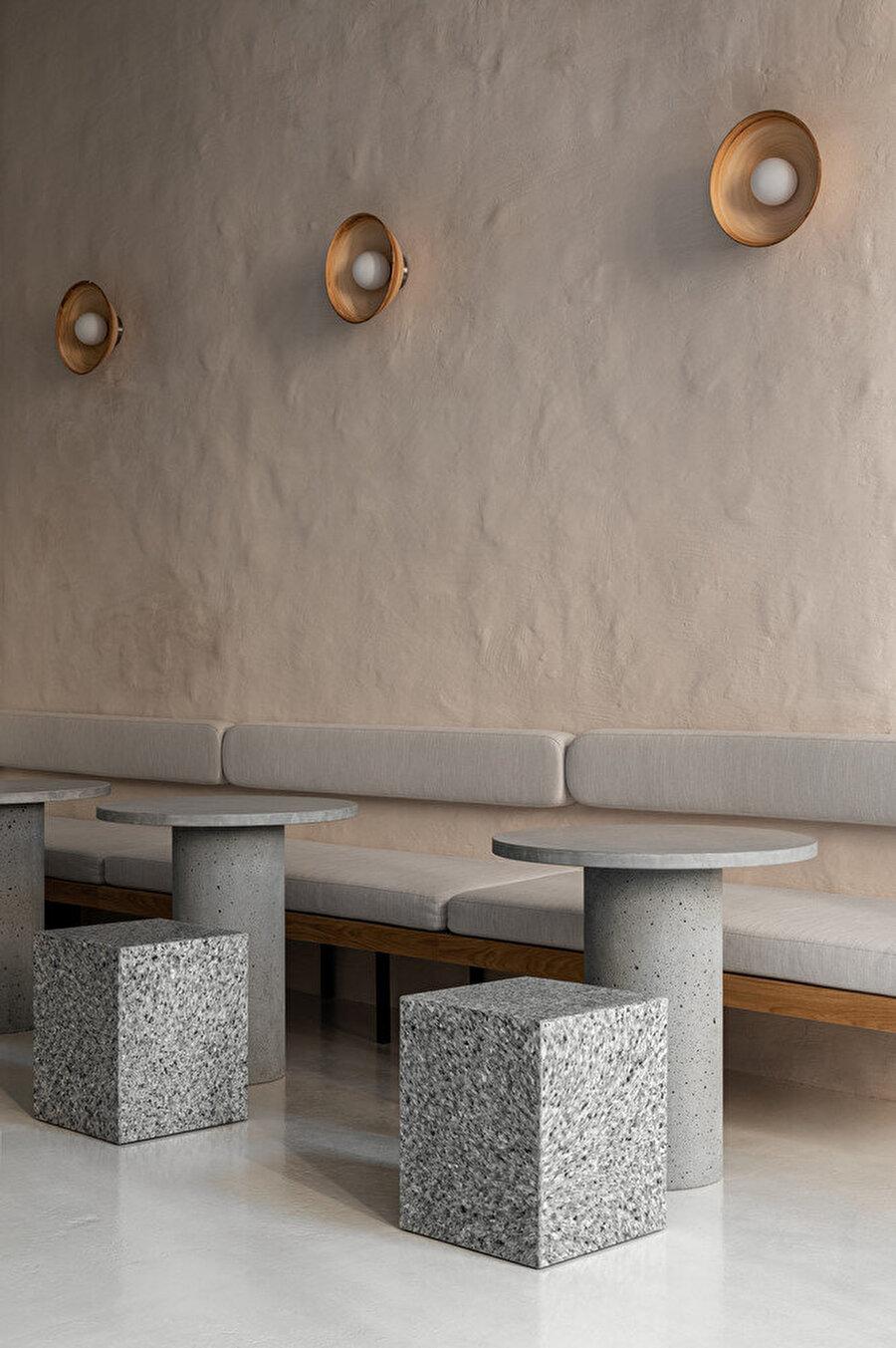 Duvarlarda bulunan bir dizi oval ahşap aplik, gün batımından sonra iç mekanı soft bir ışıkla aydınlatıyor.