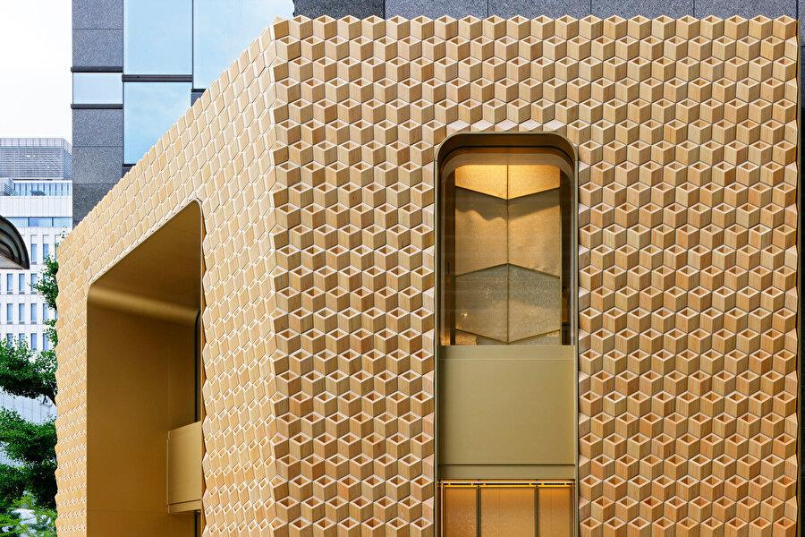 Mağazanın giriş ve pencere açıklıklarında altın renginde çerçeveler kullanılıyor.