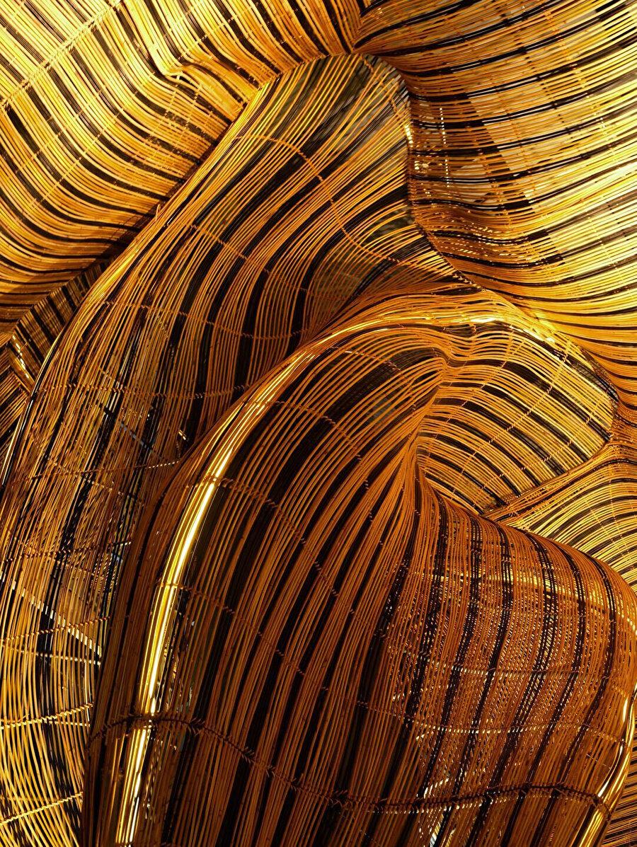 Altın rengindeki rattan ile oluşturulan akışkan geometrinin yakın çekim detayı.