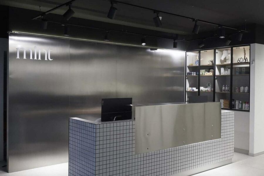 Formal ve şık bir mekân olarak tasarlanan kliniğin girişi. Karşılama bankosunda siyah derzli beyaz seramik kullanılıyor.