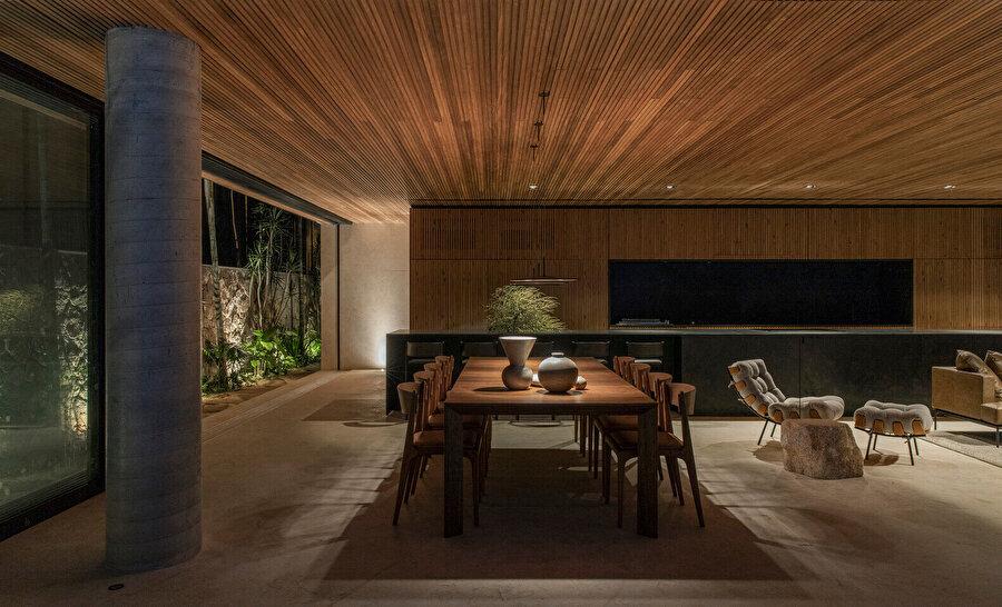 Yaşam alanındaki ahşap yemek masası, tasarım ile bütünlük sağlıyor.