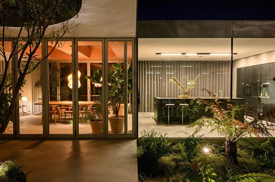 Villanın ortasındaki büyük ağaç, çevredeki mekanlarla görsel bağlantı oluşturuyor.