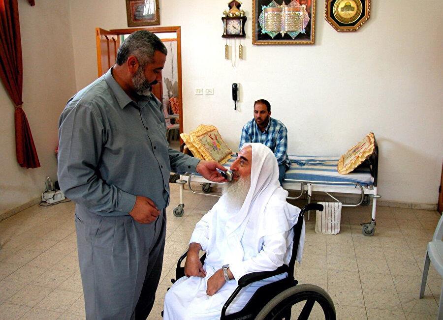İsmail Heniyye asistanlığını yaptığı Hamas'ın kurucusu Ahmed Yassin'e Gazze 'de bir telefon görüşmesi sırasında yardımcı oluyor. 13 Haziran 2003.