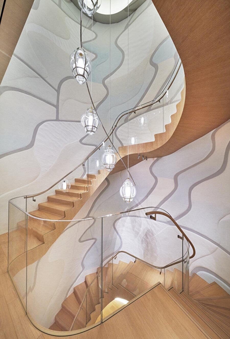 Duvardaki çalışma dört kat boyunca merdivenle birlikte yükseliyor.