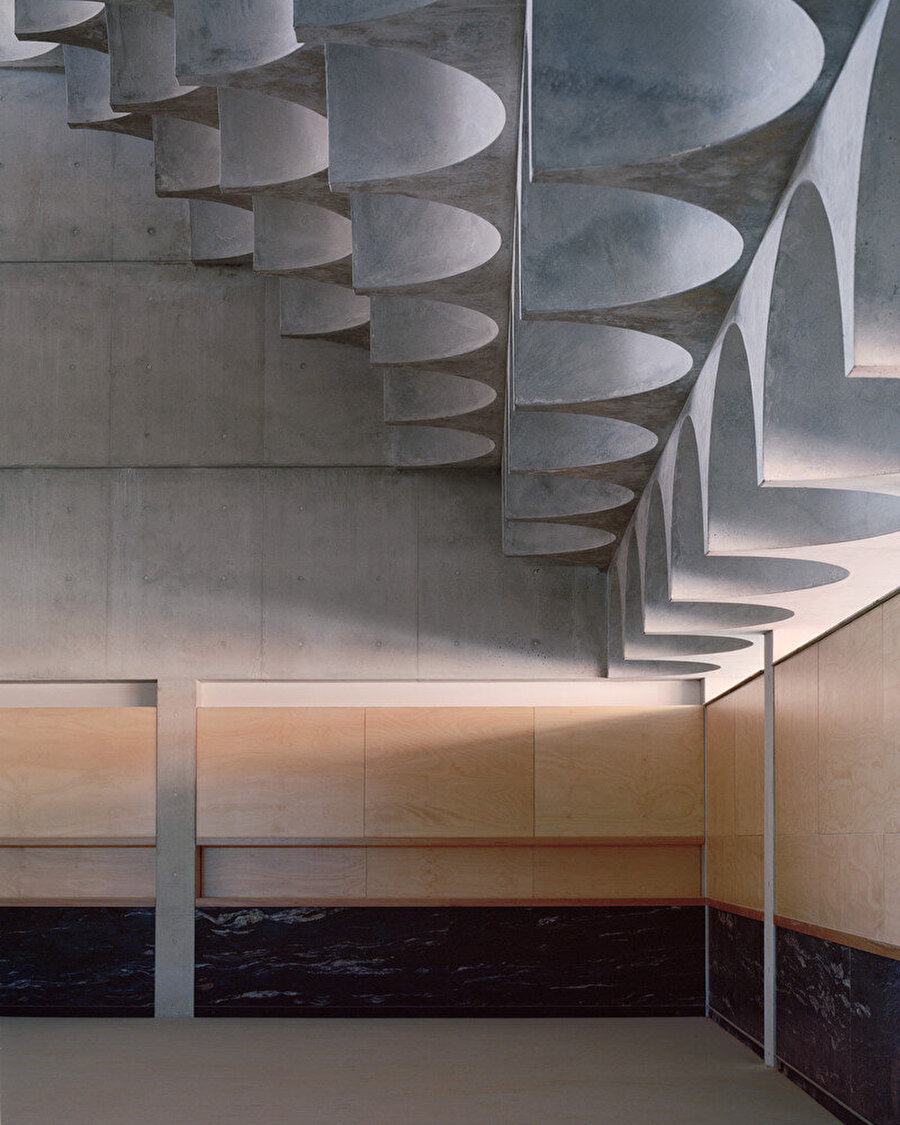 İç mekana hakim olan açık renk brüt beton yüzeyler, ahşap panellerle destekleniyor.