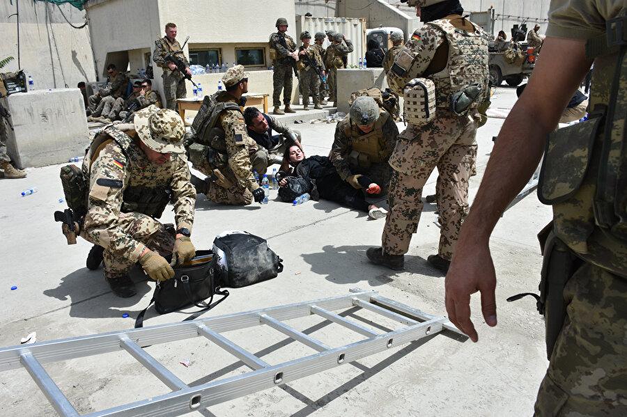 Sıcak hava ve yorgunluğun etkisiyle baygınlık geçiren bir Afganistan vatandaşı.