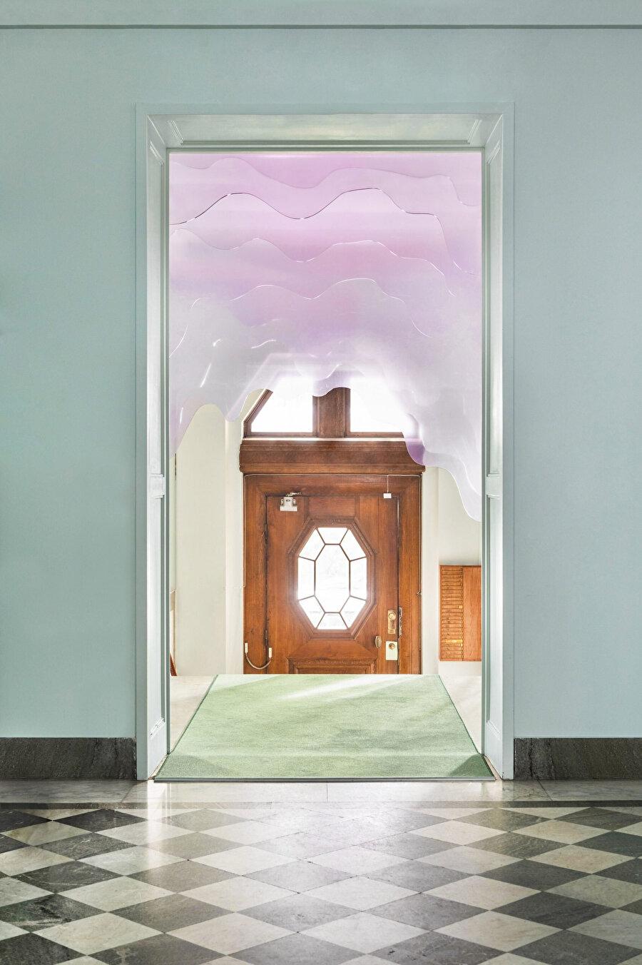 Yapının girişinde, eski ahşap kapıyı çevreleyen pleksiglas enstalasyon, el işçiliği detaylarıyla dikkat çekiyor.