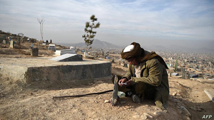 Hayatını kaybeden yakınlarının mezarı başında Kuran-ı Kerim okuyan bir Afgan.