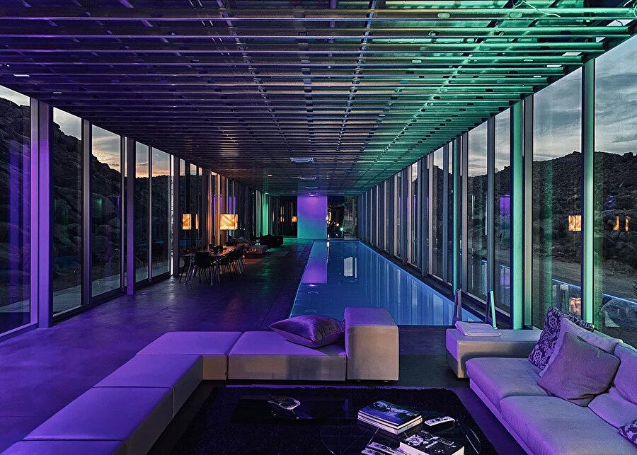 Dışarıdan gelen ışık, maviden kırmızıya, yeşil, turkuaz ve mora dönüşen havuz ışıklarıyla harmanlanarak bir tür ışık gösterisi oluşturuyor.