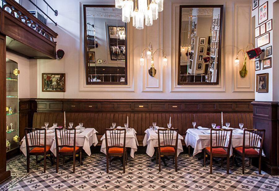 Restoranın omuz boyu eski lambriler ile kaplanmış duvarları ve yüksek tavanları.