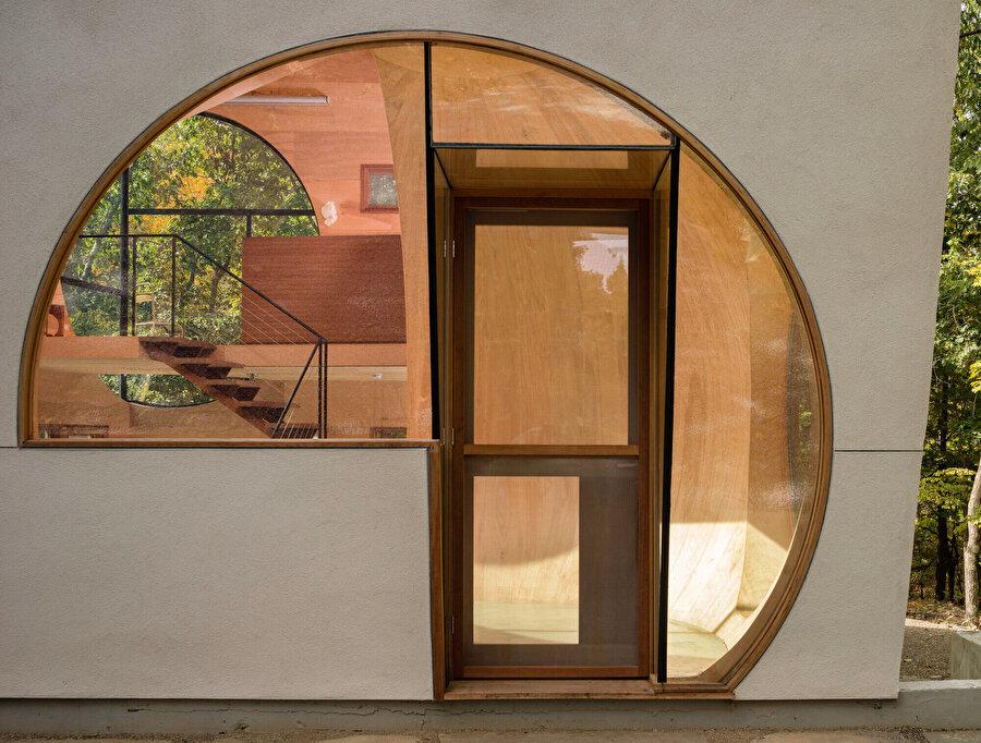 Evin girişinde yer alan dairesel açıklık, hemen içerisinde bulunan küresel boşluğu tamamlar nitelikte.