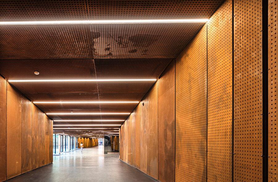 İki kışla binası, bodrum katlardan geçen geniş koridor aksıyla ortadaki amfi galerisine bağlanıyor.