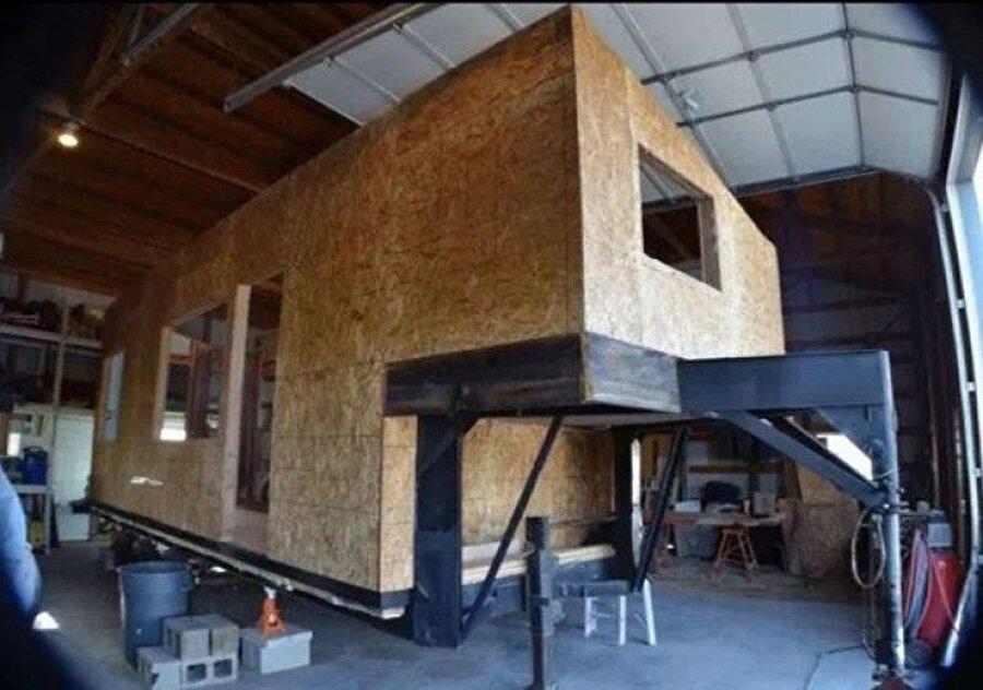 Evini yaparken kullandığı yöntem: Sürdürülebilir malzemelerle bir römorkun üzerine inşa ettiği evin dış cephesinde geri dönüşüme girmiş nakliye paletleri oldu.