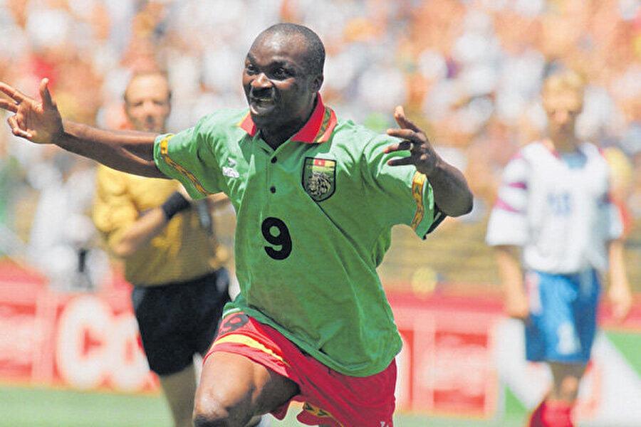 Roger Milla                                      Roger Milla     Uluslararası arenada önemli bir yıldız statüsüne ulaşan ilk Afrikalı futbolculardan biriydi. İşin daha dikkat çekici tarafı ise, bu üne, çoktan emekli olmuş olacağı, 38 yaşında ulaşmış olması. Milla, 2006 yılında Afrika Futbol Federasyonu CAF tarafından 20. Yüzyılın En İyi Afrikalı Oyuncusu seçildi.Kamerun, İtalya'da yapılan 1990 Dünya Kupası'nda tarihi bir başarı göstererek çeyrek finale yükseldi ve bunu başaran ilk Afrika ülkesi oldu. Bu başarıdaki anahtar isim de, milli takımı bırakmış olan ama oyuncuların ve teknik direktörün çabalarıyla ikna edilen Roger Milla oldu. İngiltere ile oynanan çeyrek final maçında ise sonradan oyuna girip, 1-0 geride olan takımına bir penaltı kazandırdı. Ancak maçın sonunda kazanan İngiltere oldu.     Milla'nın bu turnuvada attığı 4 gole ek olarak, o gollerden sonra korner direğinde yaptığı klasik gol sevinci de hafızalara kazındı.Milla'nın bu turnuvada attığı 4 gole ek olarak, o gollerden sonra korner direğinde yaptığı klasik gol sevinci de hafızalara kazındı.