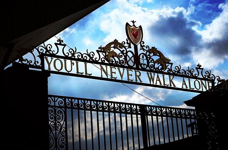 Armanın üst kısmında, kulübün resmi sloganı 'You'll never walk alone'  yer alıyor. Ayrıca bu sözlerin yer aldığı bir kapıyı andıran üst kısım, kulübün stadı Anfield Road'a açılan kapıyı temsil ediyor. Bu kapı, Liverpool tarihinin ikon isimlerinden Bill Shankly'ye ithafen 'Shankly Gates' olarak da bilinir.