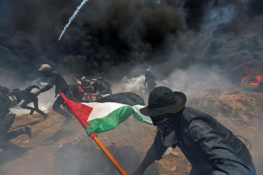 Gazze sınırında katliam Gazze'nin doğu kesiminde, sınır bölgesinde 14 Mayıs günü düzenlenen yürüyüşe İsrail askerlerinin açtığı ateş sonucu 62 Filistinli hayatını kaybetti. 2.700'e yakın Filistinlinin de yaralandığı olaylarda, sınırda beklemeye devam eden sivillerin üzerine İsrail tarafından önce göz yaşartıcı bomba atıldığı, ardından da rastgele ateş açıldığı belirtildi. Sınırda, sabahın erken saatlerinde ABD'nin Tel Aviv'deki büyükelçiliğinin Kudüs'e taşınması nedeniyle protesto gösterilerinin yapıldığı ve katılımın da büyük olduğu kaydedildi. Büyük Dönüş Yürüyüşü'nün başladığı 30 Mart'tan bu yana toplam 111 Filistinli hayatını kaybetti, 12.733 Filistinli ise yaralandı.