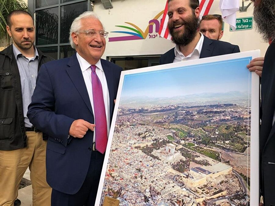 """ABD Büyükelçisi Friedman'dan skandal poz                                                                           ABD'nin İsrail Büyükelçisi David Friedman'a hediye edilen ve Mescid-i Aksa'nın olduğu alana sözde Süleyman Mabedi'nin inşa edildiğini gösteren Kudüs fotoğrafı tepkilere neden oldu. Sosyal medyada dolaşıma giren fotoğrafta, Büyükelçi Friedman'ın tepkilere neden olan fotoğrafı alırken gülümsediği görülüyor. """"Skandal"""" fotoğrafın ortaya çıkmasının ardından ABD'nin İsrail Büyükelçiliğinden konuyla ilgili yapılan yazılı açıklamada, Friedman'ın """"yaşanan olaydan büyük üzüntü duyduğu"""" belirtildi. Filistin Kurtuluş Örgütü (FKÖ) Genel Sekreteri Saib Ureykat ise yaptığı yazılı açıklamayla skandal fotoğrafa tepki göstererek, """"Büyükelçinin fotoğrafı alırken yüzünde oluşan gülümseme her şeyi açıklıyor."""" ifadesini kullandı."""