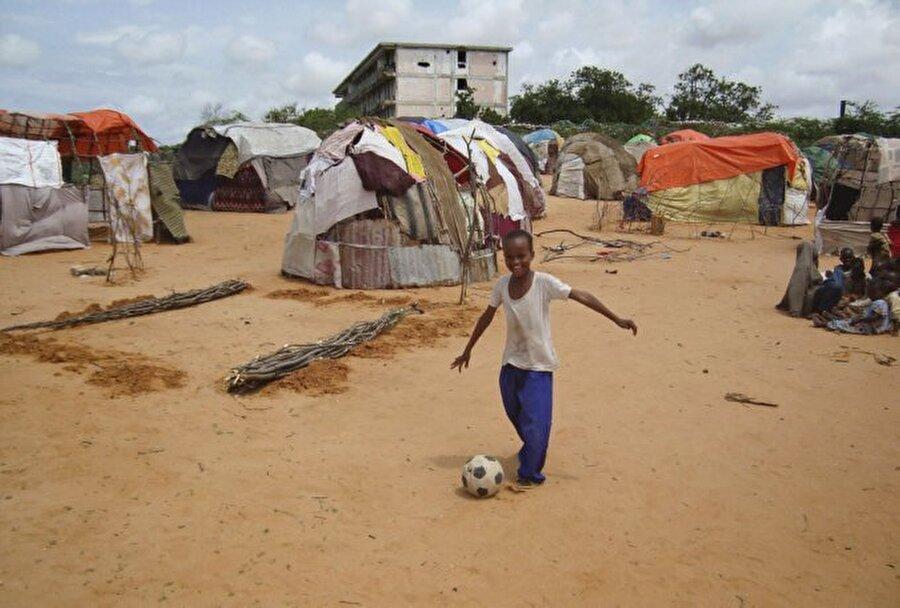 Somali  Topun peşinde koşarken yüzü gülen bu çocuğun fotoğrafı Somali'deki bir mülteci kampında çekildi.