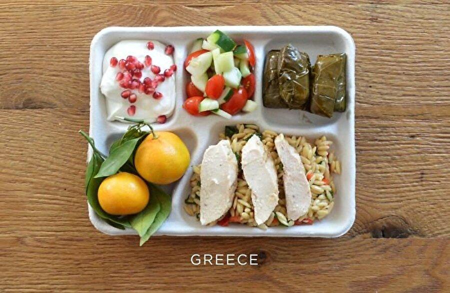 Yunanistan Yemeklerimizdeki benzerlik ile de dikkat çeken komşu Yunanistan'ın beslenme tabağında yer alan besinler: Orzo üzerinde pişmiş tavuk, zeytinyağlı sarma, domates salatası, taze portakal ve nar taneli Yunan yoğurdu.