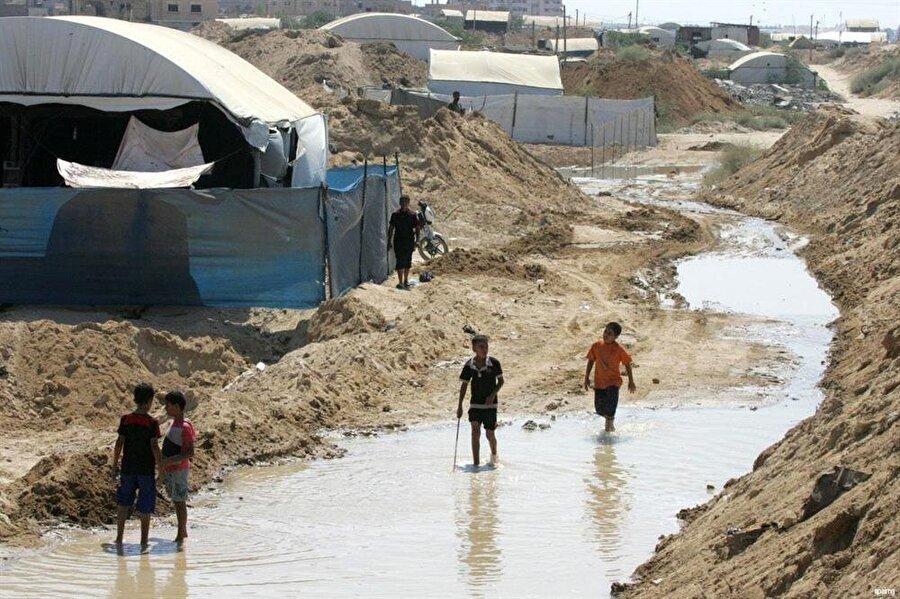 """Gazze'deki okullarda her 75 çocuğa bir tuvalet düşüyor ABD merkezli RAND Corporation isimli kuruluş tarafından yapılan bir araştırmanın sonuçlarına göre, Gazze'deki içme suyunun yüzde 97'si, temizlik standartlarını karşılamıyor. Bu suların """"içilemez"""" durumda olduğunu vurgulayan raporda, sulardaki kirlenme ve kanalizasyon karışımı nedeniyle, Gazze'de yakında salgın hastalıkların patlak verebileceği kaydedildi. Raporda, yaklaşık 2 milyon Gazze sakininin ciddi risk altında bulunduğu belirtilirken, özellikle okullardaki durumun """"felâket"""" boyutlarına ulaştığı vurgulandı. Gazze'deki öğrencilerin, temiz su eksikliğinin en büyük kurbanları olduğu açıklandı. Rapora göre, Gazze'de her 75 çocuğa bir tuvalet düşüyor."""
