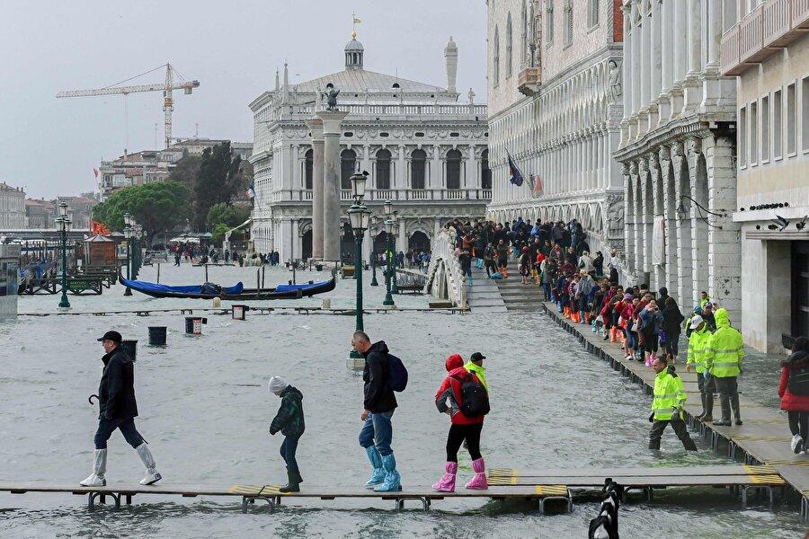 Riva degli Schiavoni'de derme çatma yapılan bir yaya köprü üzerinde suya batmamaya çalışan Venedikliler görünüyor.